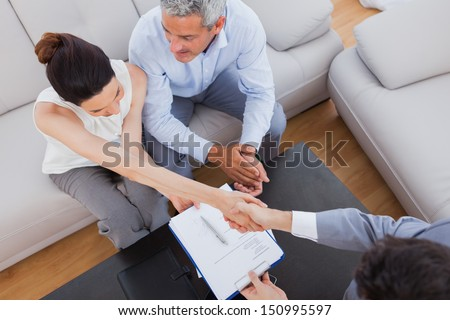 Businesswoman doing handshake with a businessman sitting on sofa at office - stock photo