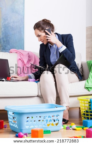 Businesswoman doing housework and calling mobile phone the same time - stock photo