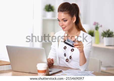 Businesswoman doing online shopping through laptop and credit card in office - stock photo