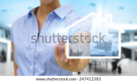 Businesswoman drawing a house with her finger on a tactile screen - stock photo