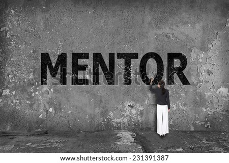 businesswoman drawing mentor on the wall - stock photo