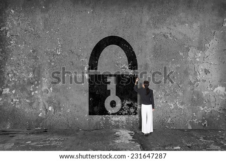 businesswoman drawing padlock on the wall - stock photo