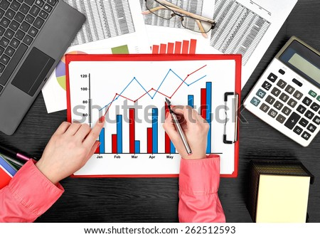 businesswoman drawing stock chart on clipboard sitting in office - stock photo
