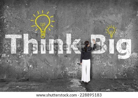 businesswoman drawing think big on the wall - stock photo