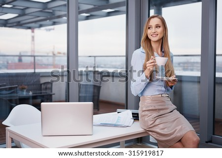 Businesswoman drinking coffee during break at office - stock photo