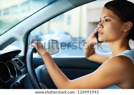 businesswoman driving car and talking on cell phone concentrating on the road - stock photo