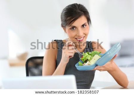 Businesswoman eating from lunch box in office - stock photo