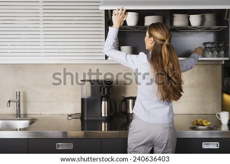 Businesswoman Getting Glass Off Shelf - stock photo