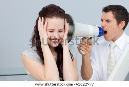 Businesswoman getting nervous with a megaphone next to her - stock photo