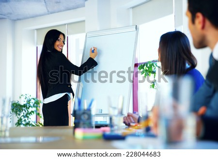 Businesswoman giving a presentation to colleagues at workplace - stock photo