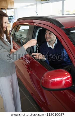Businesswoman giving car keys to a customer in a garage - stock photo