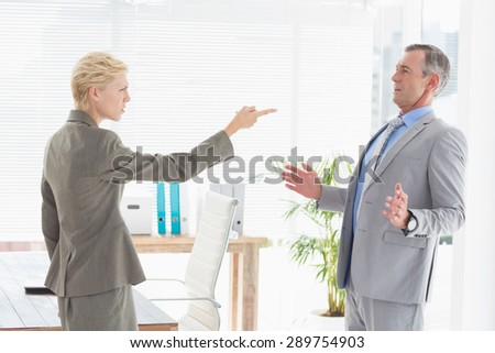 Businesswoman giving out to her boss in an office - stock photo