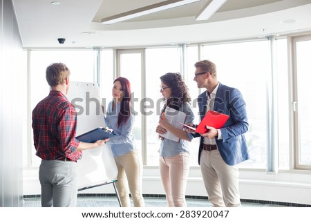 Businesswoman giving presentation to colleagues in creative office - stock photo