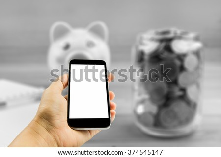 businesswoman hand holding a phone ,mobile,smartphone,tablet,labtop with isolated screen against over blurred image of coin in glass bottle,business concept - stock photo