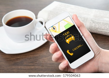 businesswoman hand holding a phone with interface taxi against the background of the table in the office - stock photo