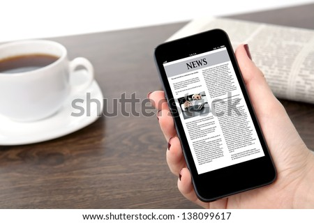 businesswoman hand holding a touch phone with business news on a screen against the background of the table in the office - stock photo