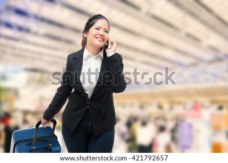 businesswoman hand holding tablet while carrying luggage - stock photo