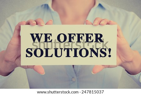 Businesswoman hands holding white card sign with we offer solutions! text message isolated on grey wall office background. Retro instagram style image - stock photo