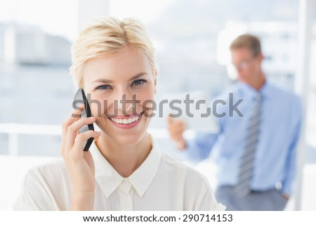 Businesswoman having a phone call with colleague in background in an office - stock photo