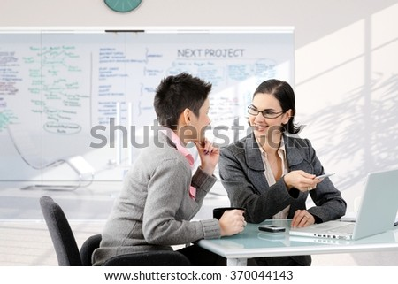 Businesswoman having discussion at work sitting at office desk, smiling. - stock photo