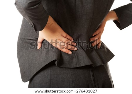 Businesswoman having huge back pain - stock photo