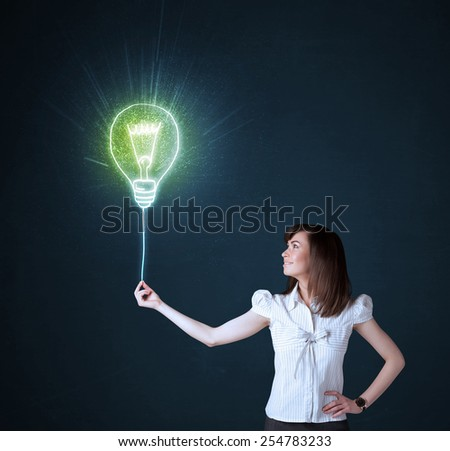 Businesswoman hold a shining idea bulb on a blue background - stock photo