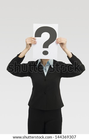 Businesswoman holding a card with question mark in front of a face - stock photo