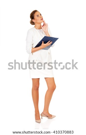 Businesswoman holding a clipboard and thinking about something - stock photo