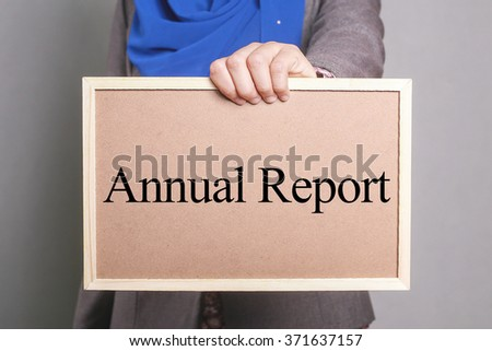 Businesswoman holding a softboard written Annual Report - stock photo