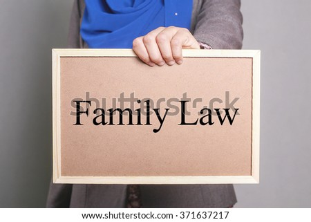 Businesswoman holding a softboard written Family Law - stock photo