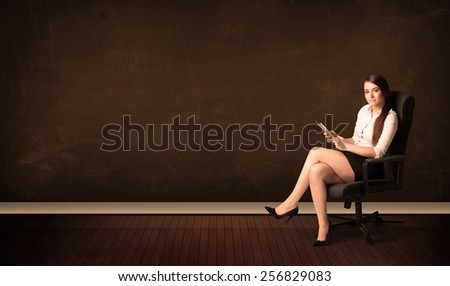 Businesswoman holding high tech tablet on brown background with copyspace - stock photo