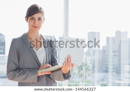 Businesswoman holding laptop by a large window - stock photo