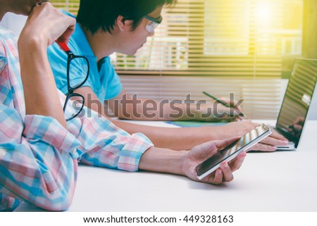 Businesswoman holding mobile phone and businessman writing data on paper about meeting subject for discuss at meeting room, business content ,business concept and selective focus,film effect. - stock photo