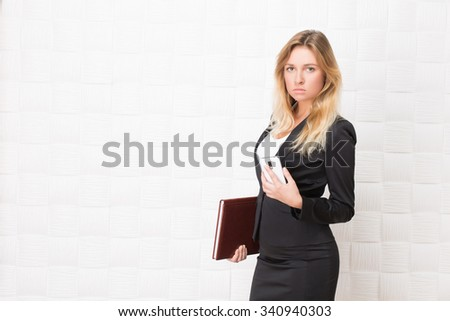 Businesswoman holding mobile phone and folder with documents in the office. Serious blond lady in business suit looking at the camera. - stock photo