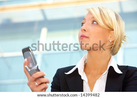 Businesswoman holding mobile phone, contemplating - stock photo