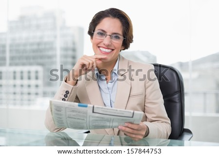 Businesswoman holding newspaper at her desk in bright office - stock photo