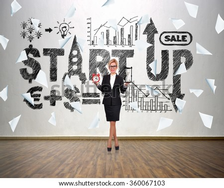 Businesswoman holding sandglass and alarm clock in hand. Drawing start up concept and falling many blank paper. - stock photo