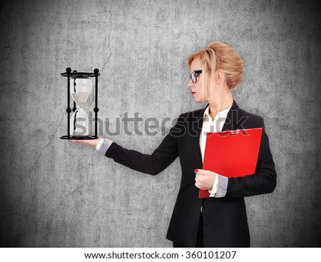 businesswoman holding sandglass and red clipboard on a concrete wall background - stock photo