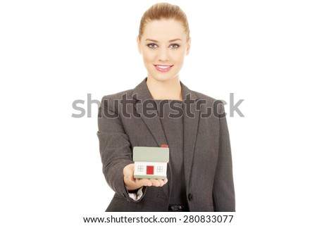 Businesswoman holding small model house. - stock photo