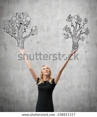 businesswoman holding two drawing business tree - stock photo