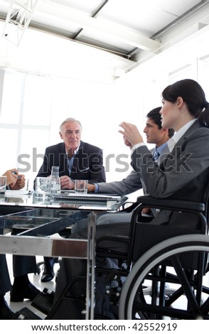 Businesswoman in a wheelchair during a meeting with her team - stock photo