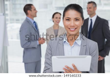 Businesswoman in bright office using her tablet pc while colleagues talking together - stock photo