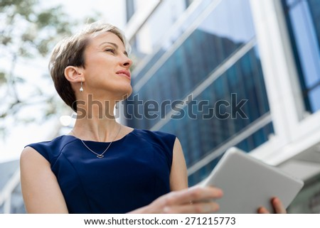 Businesswoman in city holding his notebook - stock photo
