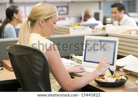 Businesswoman in cubicle using laptop and eating salad - stock photo