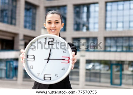businesswoman in front her office building showing time - stock photo