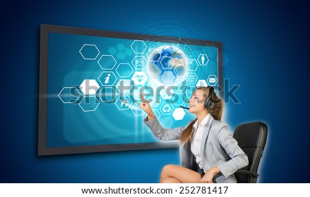 Businesswoman in headset pressing touch screen button on virtual interface with honeycomb shaped icons and Globe with radiant figures, on blue background. Element of this image furnished by NASA - stock photo
