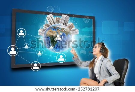 Businesswoman in headset using touch screen interface featuring Globe with buildings on top, network of person icons and other elements, on blue background. Element of this image furnished by NASA - stock photo