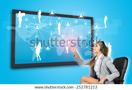 Businesswoman in headset using touch screen interface featuring world map, network of person icons and female silhouettes, on blue background - stock photo