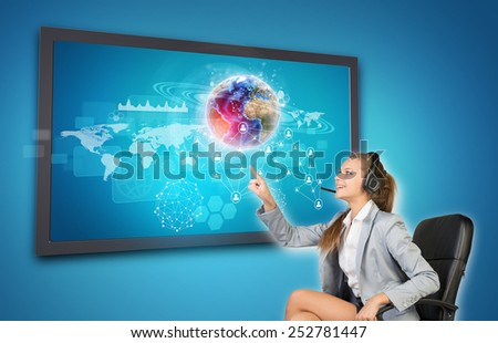 Businesswoman in headset using touch screen interface with Globe, network of person icons and other elements, on blue background. Element of this image furnished by NASA - stock photo