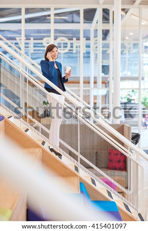 Businesswoman in modern office space using phone on stairs - stock photo